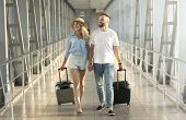 Traveling Concept. Happy Couple In Casual Wear Going In Airport Terminal With Luggage poster