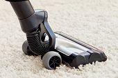 Close Up Of Modern Vacuum Cleaner On Beige Carpet On Floor In Living Room, Copy Space. Housework, Ho poster