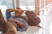 Traveler Waiting At The Airport Departure Area For His Delay Flight.  Young Traveler Sleeping On The poster