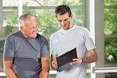 Fitness trainer explaining training plan to senior man in gym
