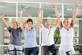 Happy cheering senior group in fitness center on spinning bikes