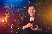 Young Asian Male Bartender Mixing Alcohol Drink Cocktail In Glass Wine At Outdoors Night Club. Peopl poster