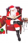 Humorous closeup of Santa Claus (that jolly old elf that  lives at the North Pole) reading and writi