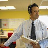 Empresário com fone de ouvido segurando o caderno