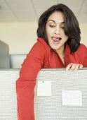 Indian businesswoman reaching over cubicle wall