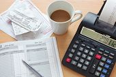 Still life bookkeeping photo of a sales ledger with a pile of receipts, invoices and a print calcula
