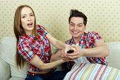 Retrato de la joven pareja con control remoto frente a TV set