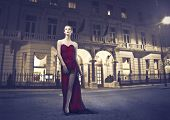 Beautiful elegant woman standing in front of a luxury palace