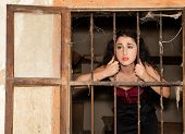 Sad woman in prison behind bars of a derelict building