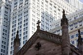 The Tops Of Spires Of Trinity Church With Modern Buildings Behind In New York City.
