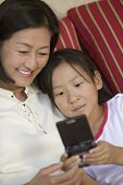 Mother and Daughter Playing Handheld Video Game