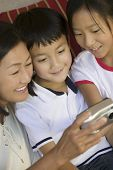 Mother and Children Looking at Digital Camera