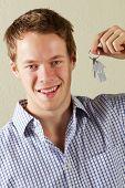 Studio Shot de jovem segurando as chaves para a primeira casa