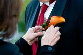 Colocando o corpete em um noivo durante um casamento