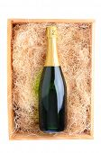 Overhead shot of a single champagne bottle in a wood shipping crate filled with packing straw. Verti