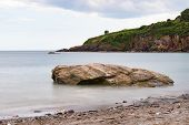 Smooth, Calm Sea Around A Shoreline Rock At St Marys Bay Beach In Torbay, Devon, With Some Coastline poster