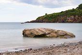 Smooth, Calm Sea Around A Shoreline Rock At St Marys Bay Beach In Torbay, Devon, With Some Coastline poster