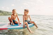 Two Smiling Caucasian Boys Kids Sitting On Paddle Sup Surfboard In Water. Children Friends Talking L poster
