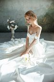 Girl In A Chic Long Dress Sitting On The Floor. White Wedding Dress On The Brides Body. Beautiful L poster