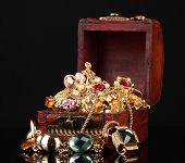 picture of treasure chest  - Wooden chest full of gold jewelry on black background - JPG