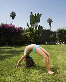 Hispanic girl doing backbend in grass