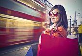 Sonriendo a hermosa mujer llevar algunas bolsas con londoner calle en segundo plano
