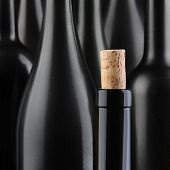 Closeup of a wine bottle with the cork partially out, in front of an out of focus group of larger bo