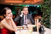 picture of boring  - young woman bored to date while her boyfriend having business cell on mobile phone - JPG