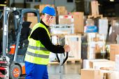 Warehouseman in protective vest pulls a mover with packages and boxes at warehouse of freight forwar