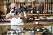 Middle-aged merchant aiming with rifle in gun shop