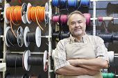 Portrait of a happy middle-aged salesperson standing in front of electrical wire spool with arms cro
