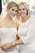 pic of half-dressed  - Portrait of a mother with daughter dressed as bride in bridal store - JPG