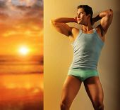 Sexy portrait of an active young fit male model in underwear and tank against wall near glorious sunrise in golden light