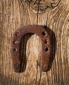 Antique horseshoe luck symbol rusted on vintage wood background