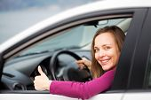 Happy attractive woman sitting in car and looking at camera