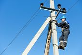 stock photo of work crew  - Electrician lineman repairman worker at climbing work on electric post power pole - JPG