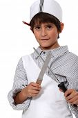 Young boy dressed as a butcher sharpening a knife