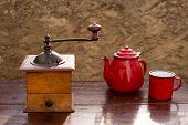Retro alte Kaffeemühle mit Vintage Teekanne und rote Tasse