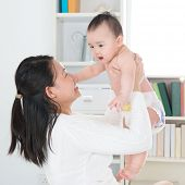 Asian mother and six months old baby girl at home.