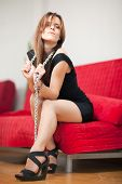picture of sado-masochism  - young beautiful woman sitting on a red couch and holding a steel chain - JPG