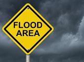image of precaution  - A road warning sign against a stormy sky with words Flood Area Flood Warning - JPG