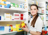 Pharmacist Holding Out Tablets In Bottle At Drugstore