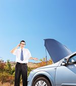 Young businessman standing near a broken car and talking on a mobile phone, shot with a tilt and shi