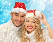 christmas, x-mas, winter, happiness concept - family couple in sweaters and santa's hats