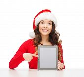 christmas, x-mas, electronics, gadget concept - smiling woman in santa helper hat with blank screen tablet pc