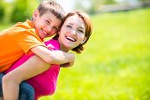 stock photo of schoolboys  - Happy mother and son in the spring meadow outdoor portrait - JPG