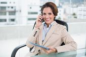 Happy businesswoman calling with smartphone in bright office