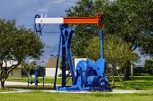 stock photo of nod  - A red white and blue nodding donkey pumpjack used for taking oil from the ground - JPG