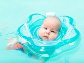 Baby swimming with neck swim ring in pool
