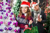 Portrait of happy young woman carrying shopping bag at Christmas store with man in background